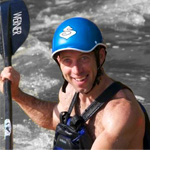 Photo of Jason Beakes smiling at the camera while paddling